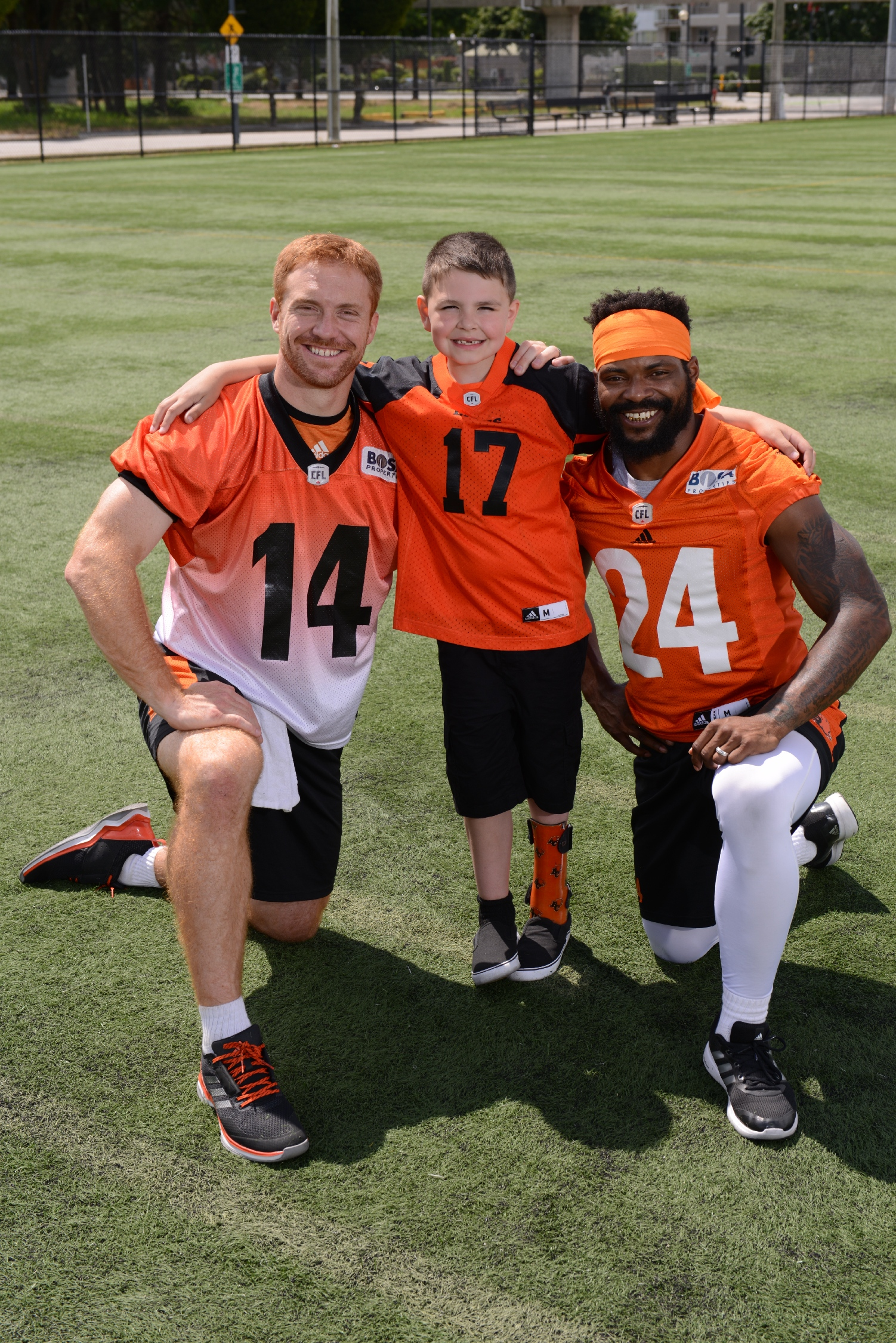 Darevin teams up with BC Lions players Travis Lulay (#14) and Jeremiah Johnson (#24).