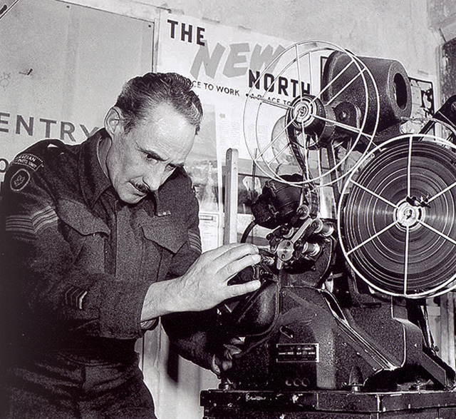 Sgt. D. Newands handles a projector at Merton Park Studios. Location: London. (LAC PA# 152105)