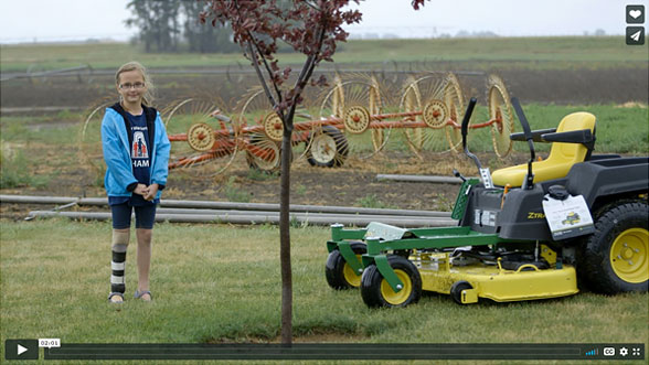 Neveah standing in a field with a lawn mower