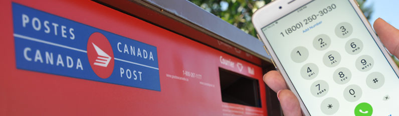 A person holds a cell phone with the War Amps phone number 1 800 250-3030 displayed in front of a Canada Post mailbox.